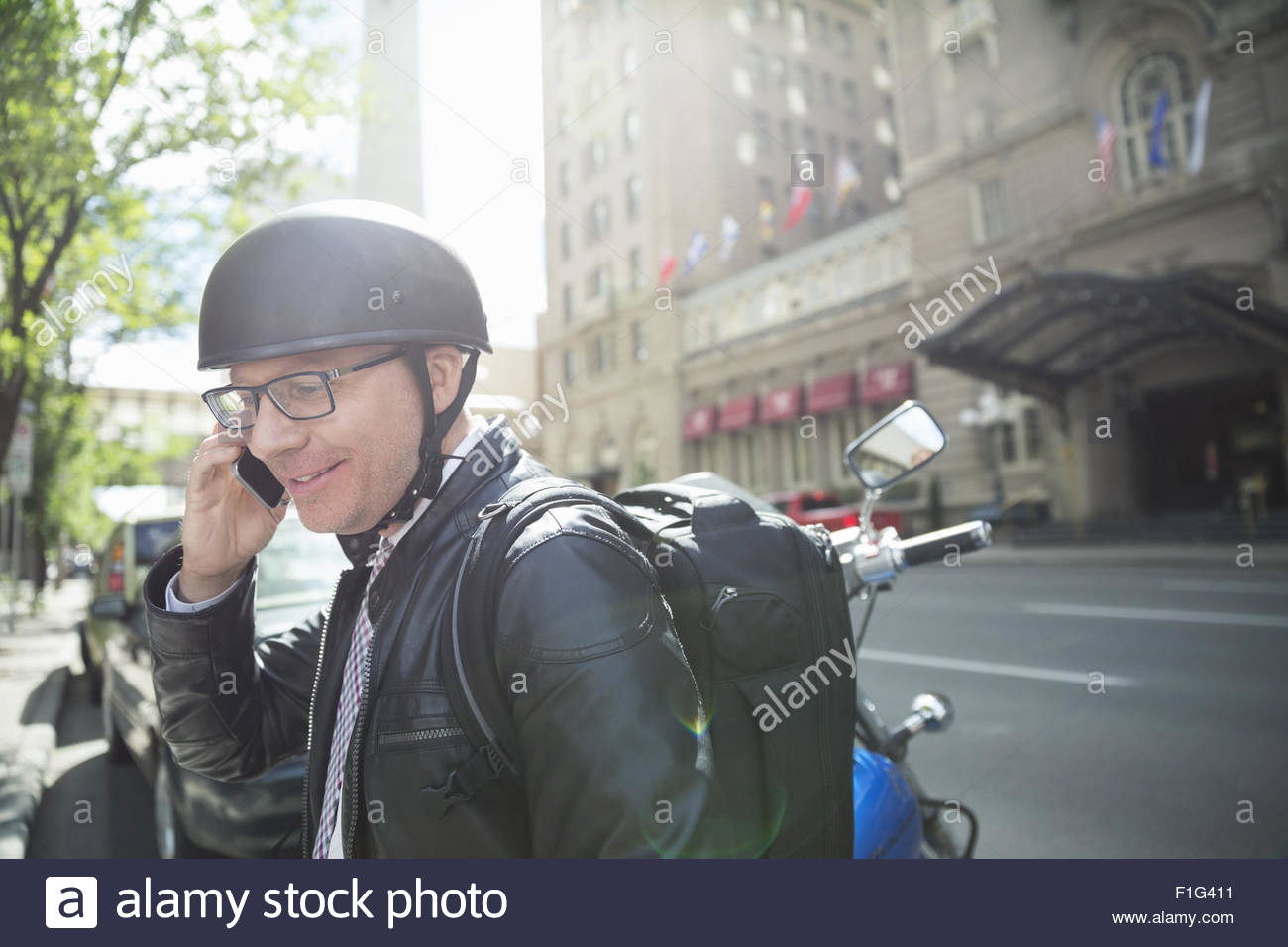 Businessman commuting with motorcycle talking cell phone - Stock Image