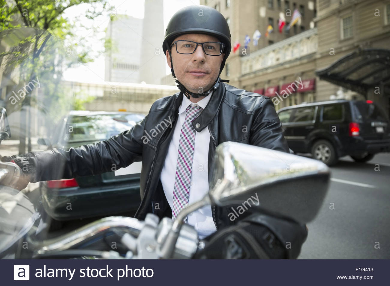Portrait confident businessman commuting on motorcycle - Stock Image