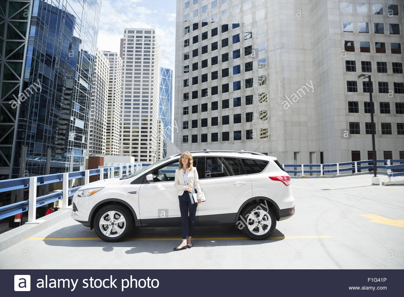 Portrait businesswoman outside car in city parking lot - Stock Image