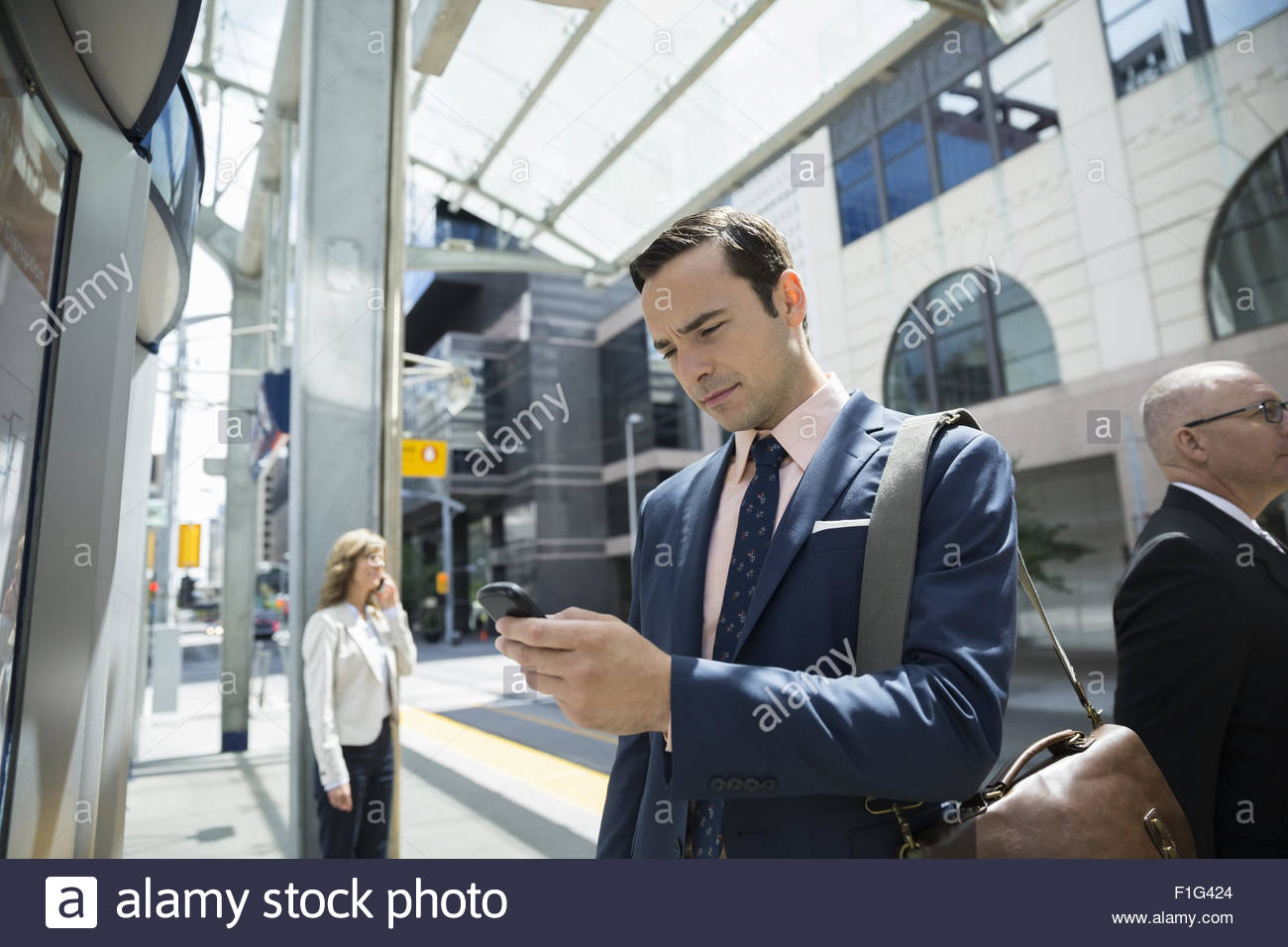 Businessman texting with cell phone at train station Stock Photo