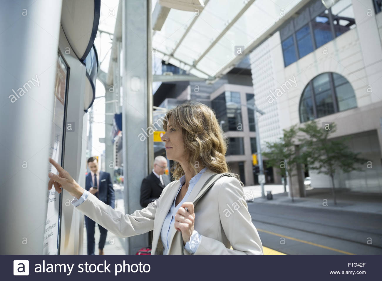 Businesswoman checking train schedule in city - Stock Image