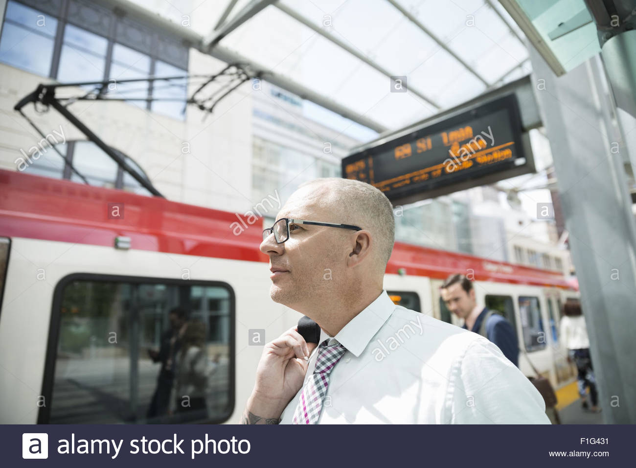 Businessman at train station platform - Stock Image