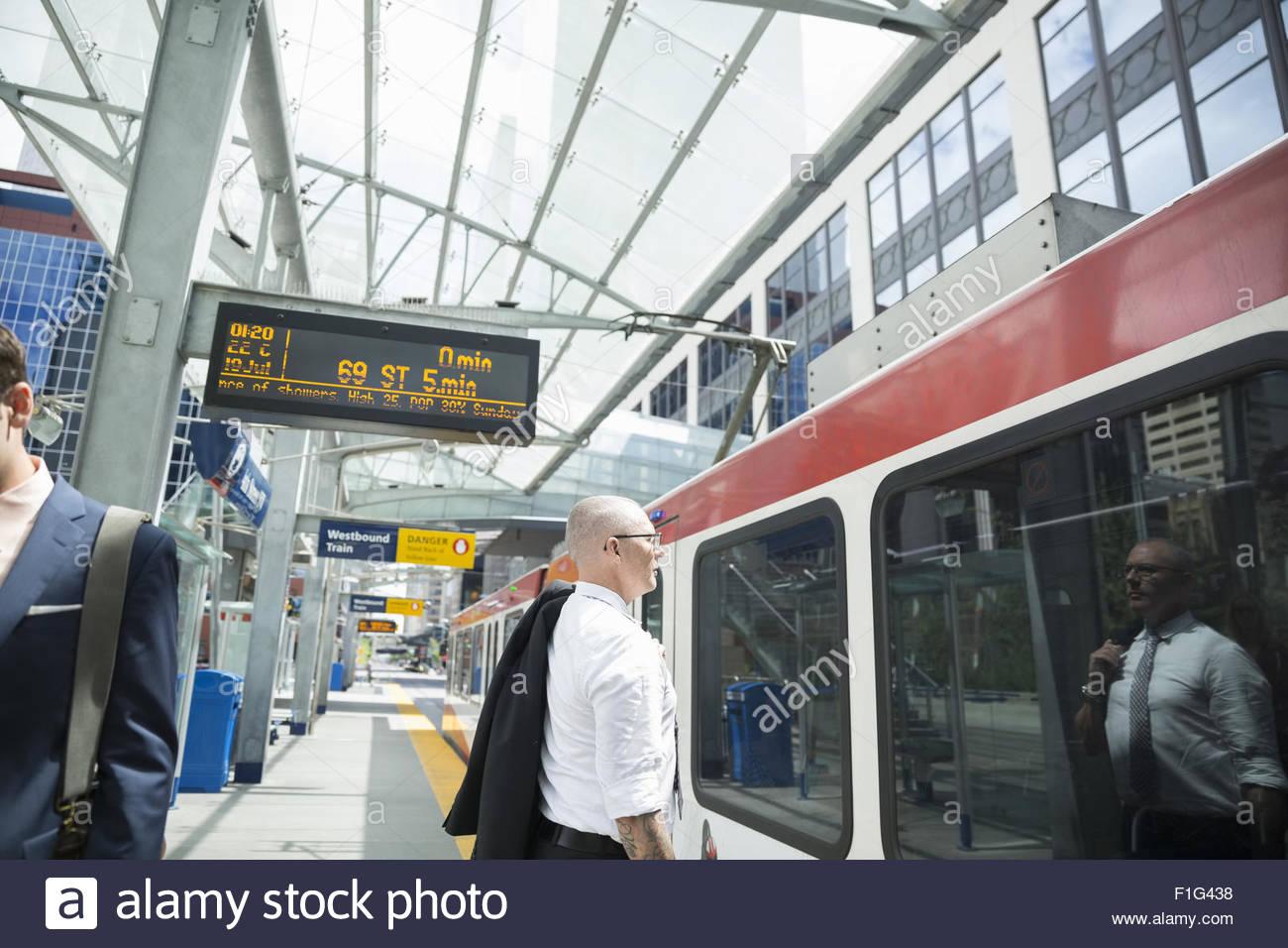 Businessman at commuter train on platform - Stock Image