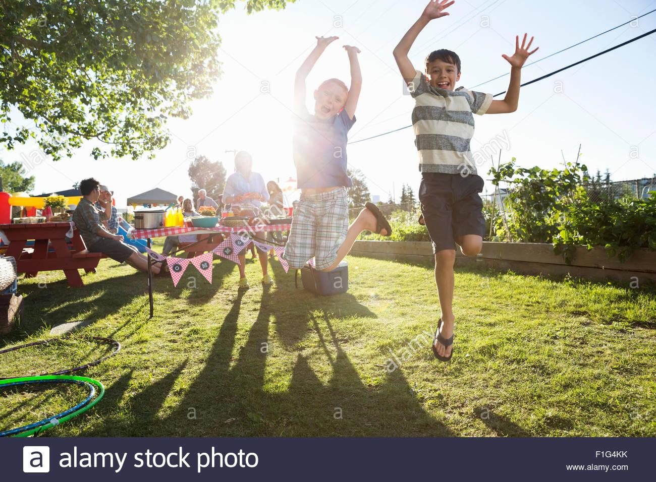Portrait playful boys jumping for joy sunny park - Stock Image