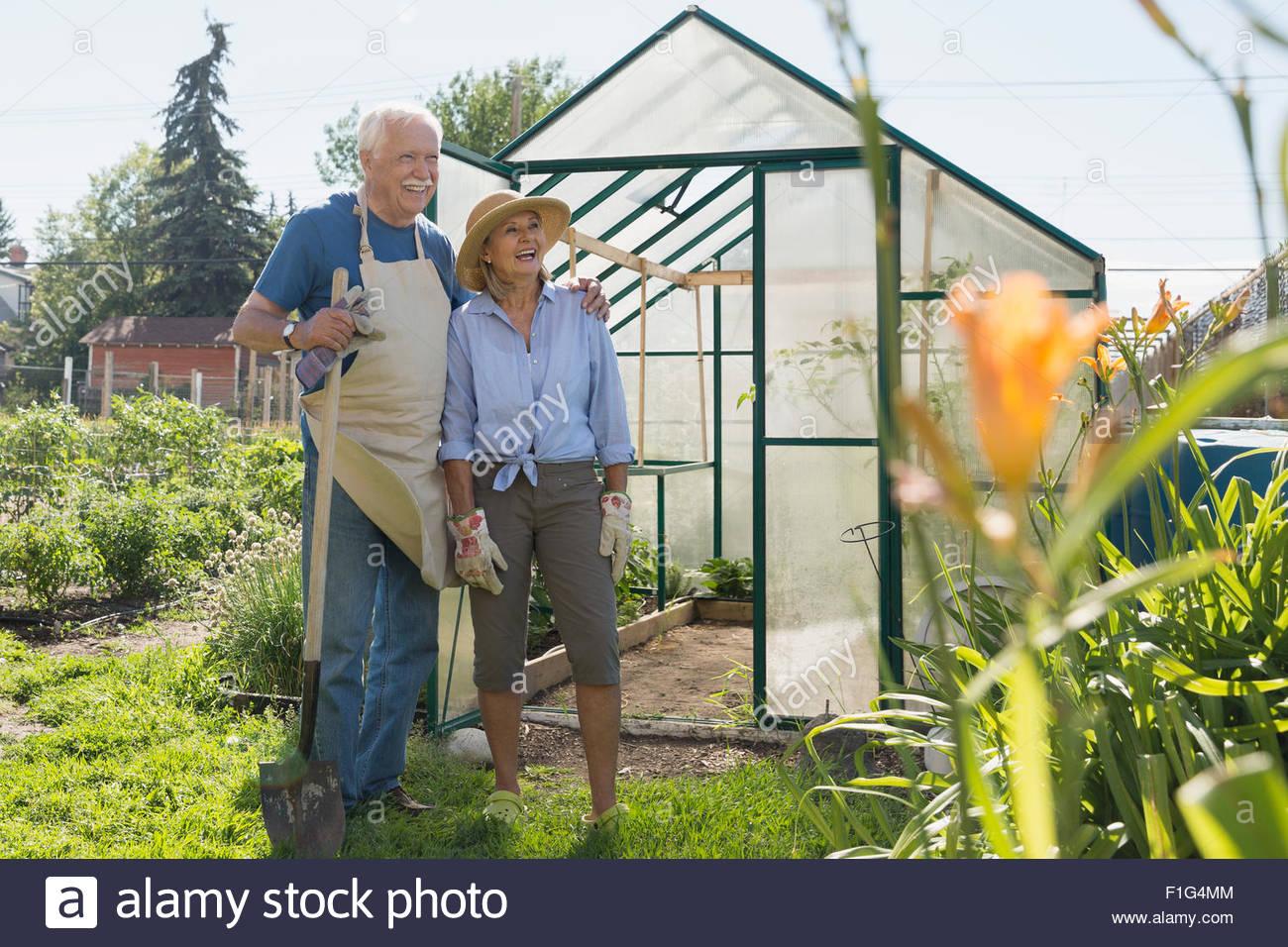 Senior couple with shovel at garden greenhouse - Stock Image