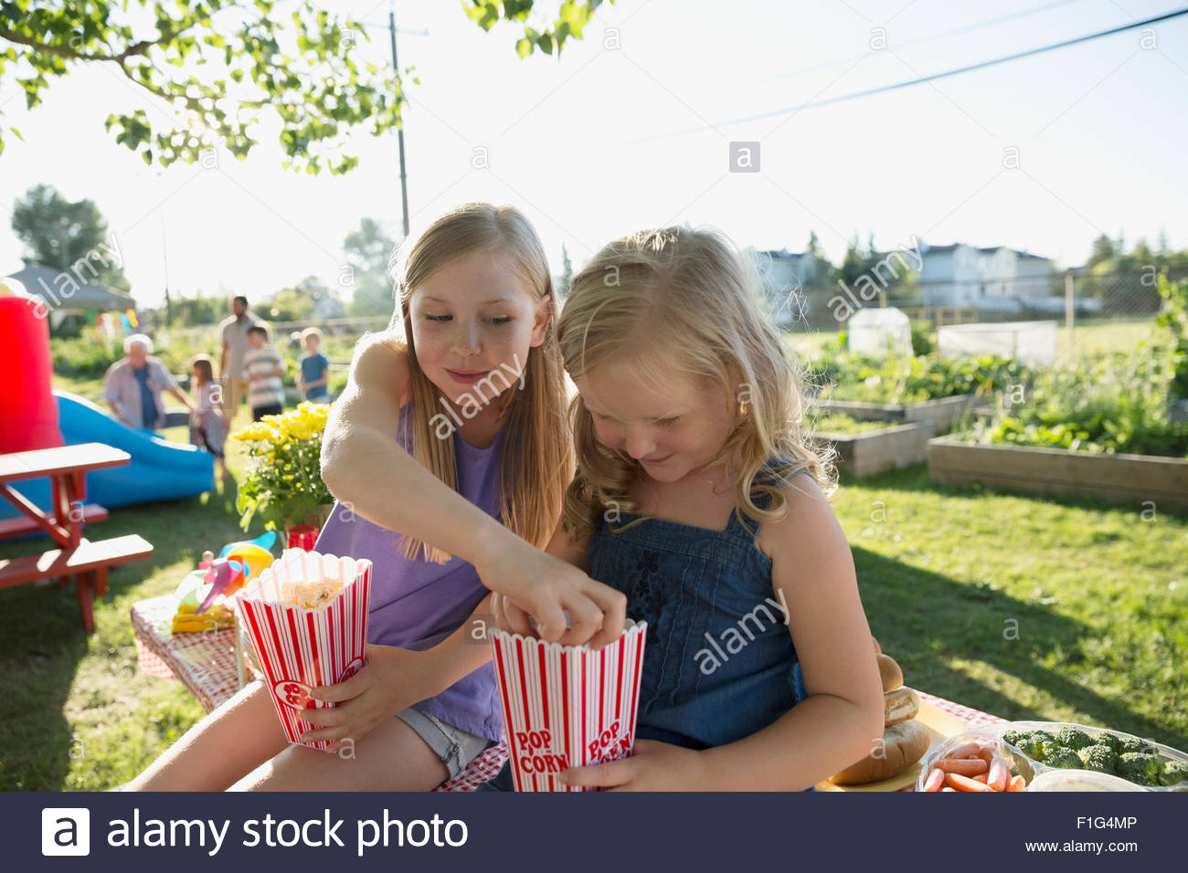 Sisters sharing popcorn in park - Stock Image
