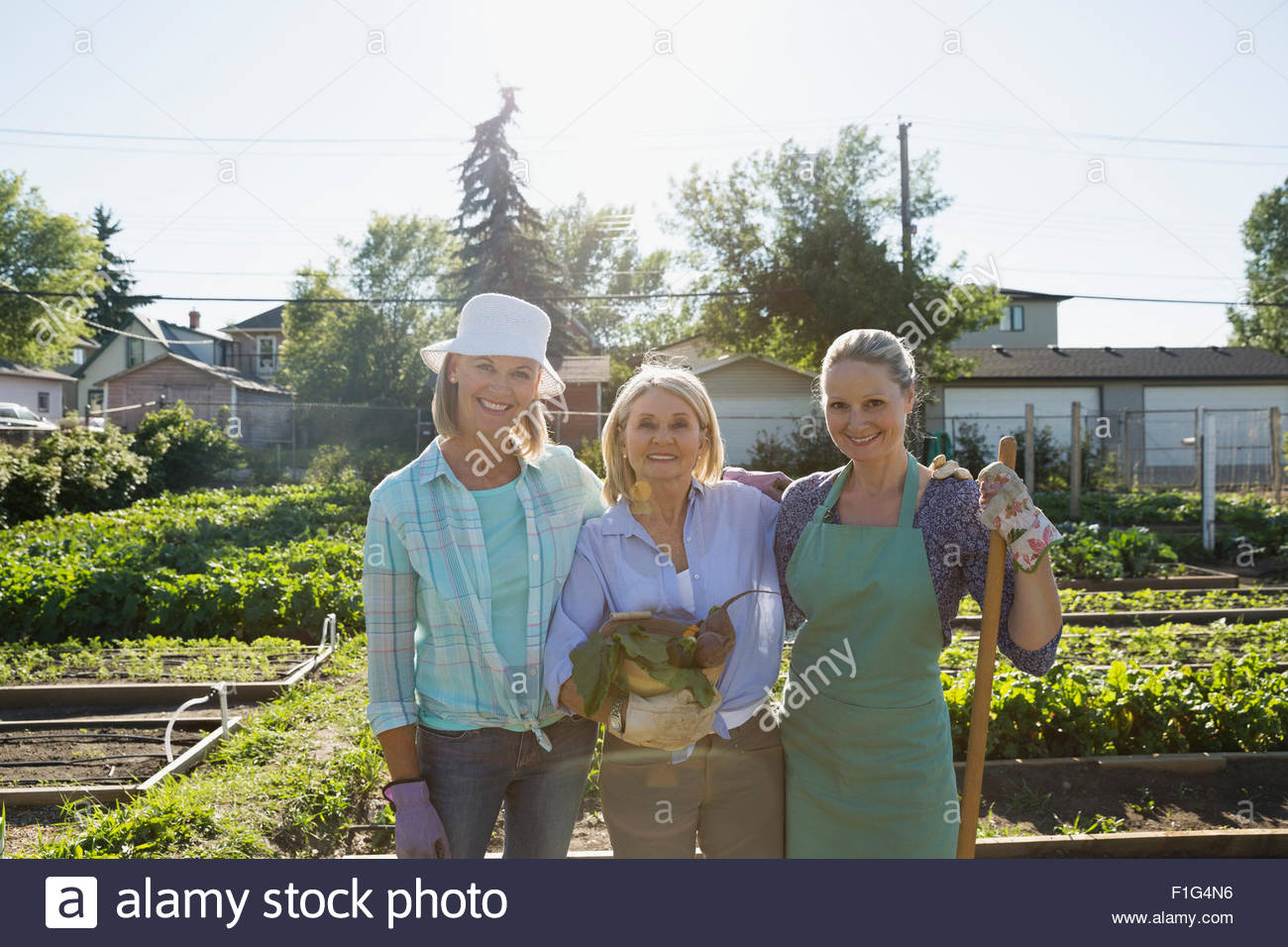 Portrait smiling women in sunny community vegetable garden - Stock Image
