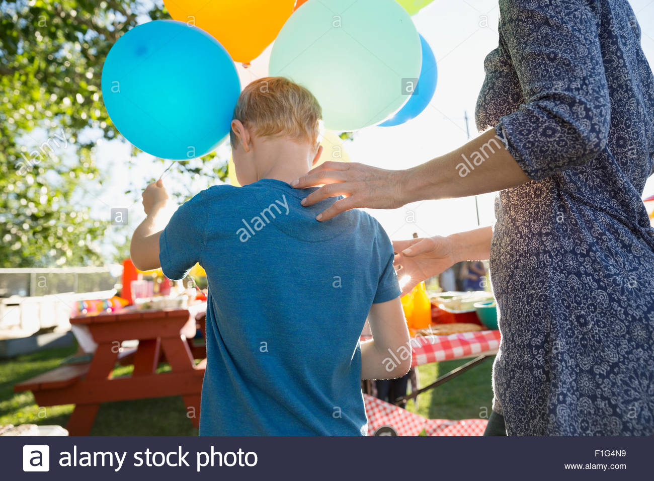 Mother and son with balloons in park - Stock Image