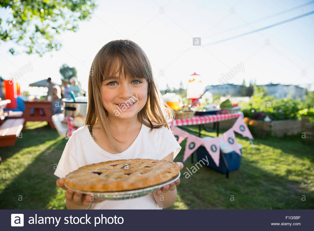 Portrait smiling girl holding fresh baked pie park - Stock Image