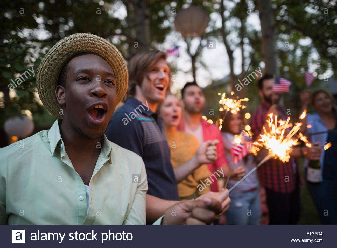 Friends with sparklers cheering 4th of July party - Stock Image