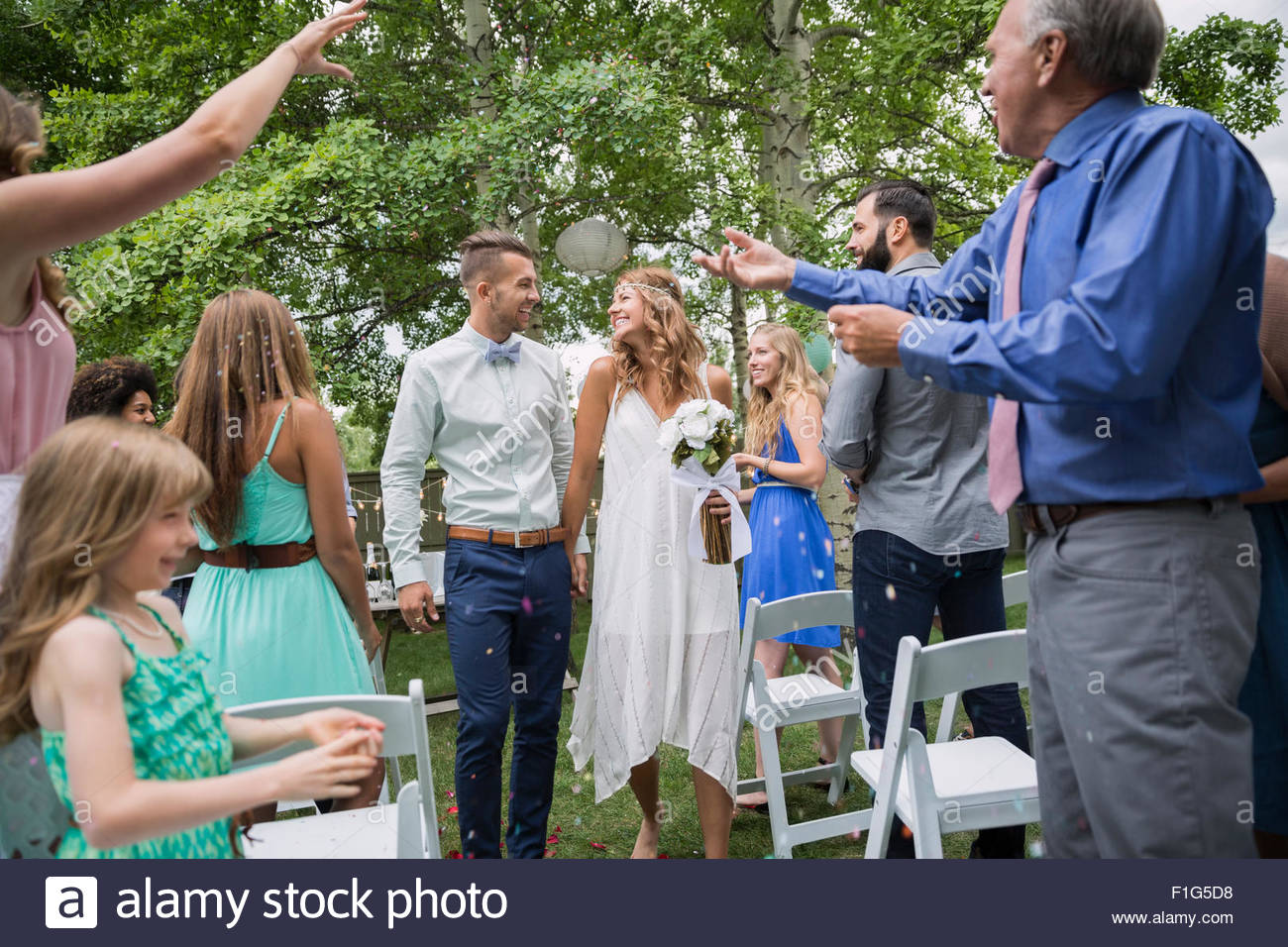 Guests throwing confetti over bride groom backyard wedding - Stock Image