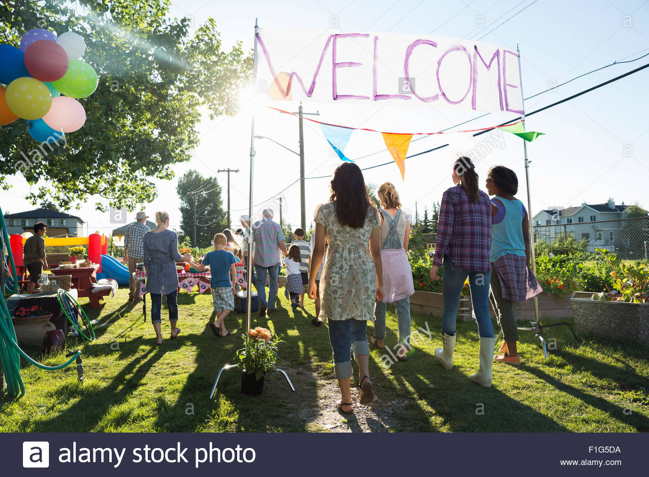 Neighbors entering under Welcome sign party in park - Stock Image