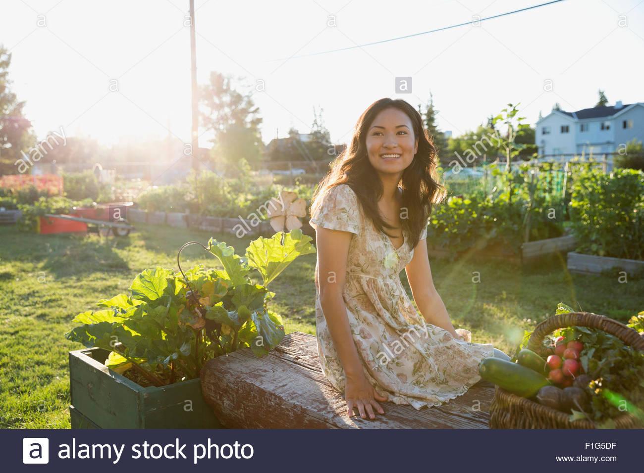 Smiling teenage girl harvesting vegetables in garden - Stock Image