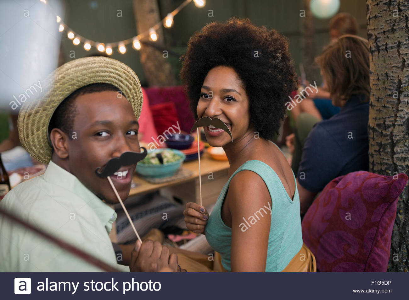 Portrait playful couple with fake mustaches on sticks - Stock Image