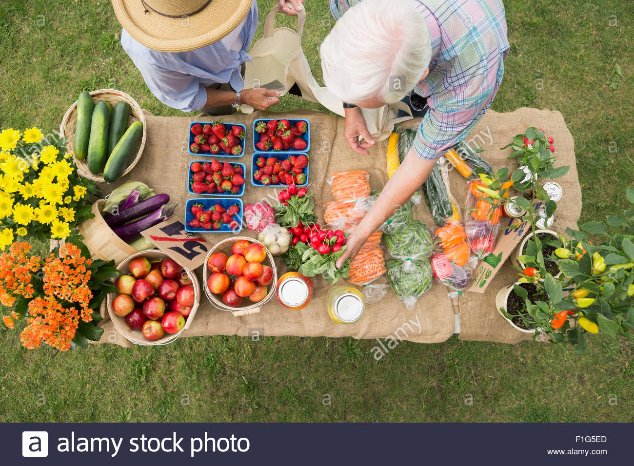 Shoppers reaching produce on farmers market display table - Stock Image