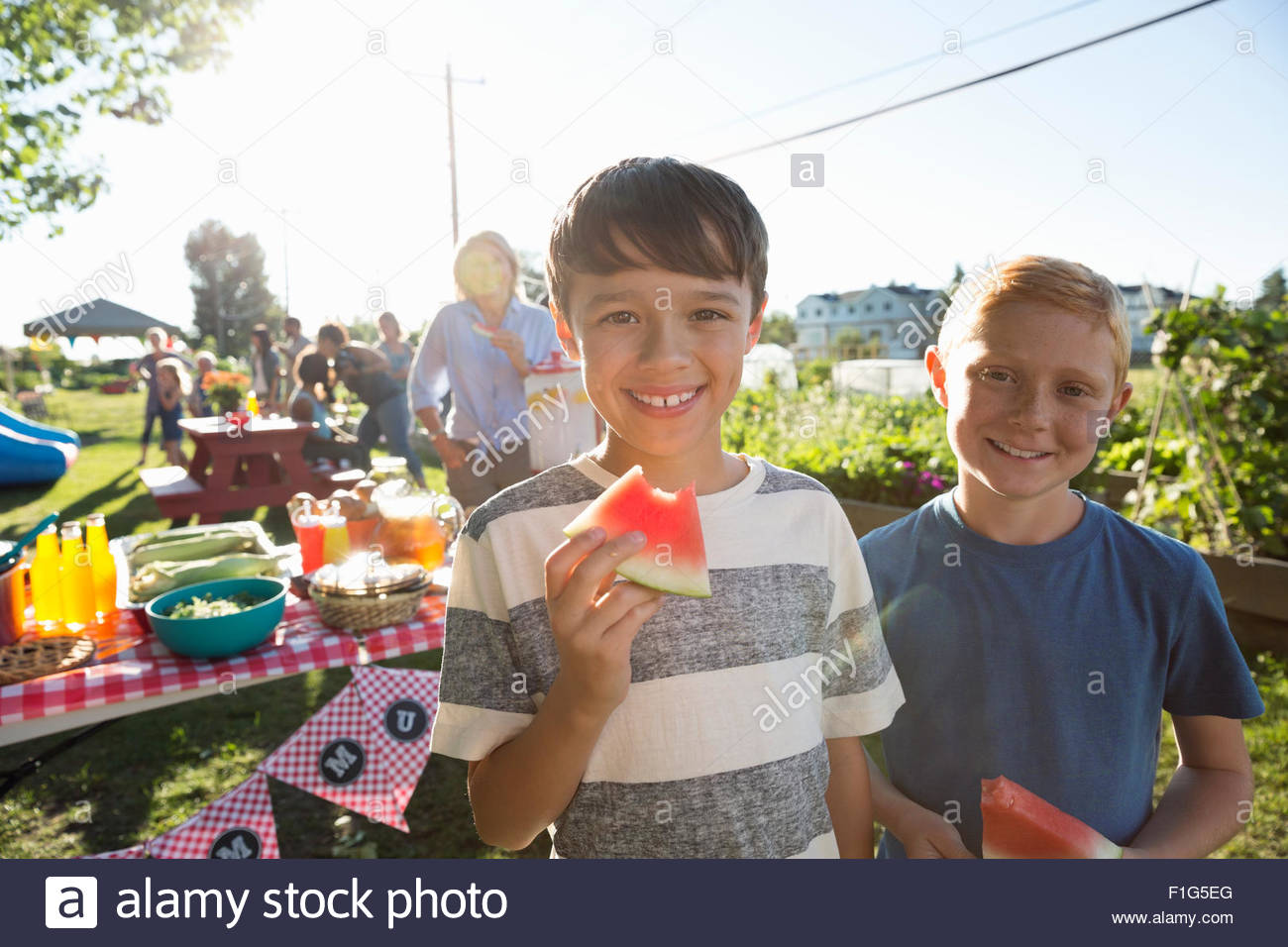 Portrait smiling boys eating watermelon sunny park party - Stock Image