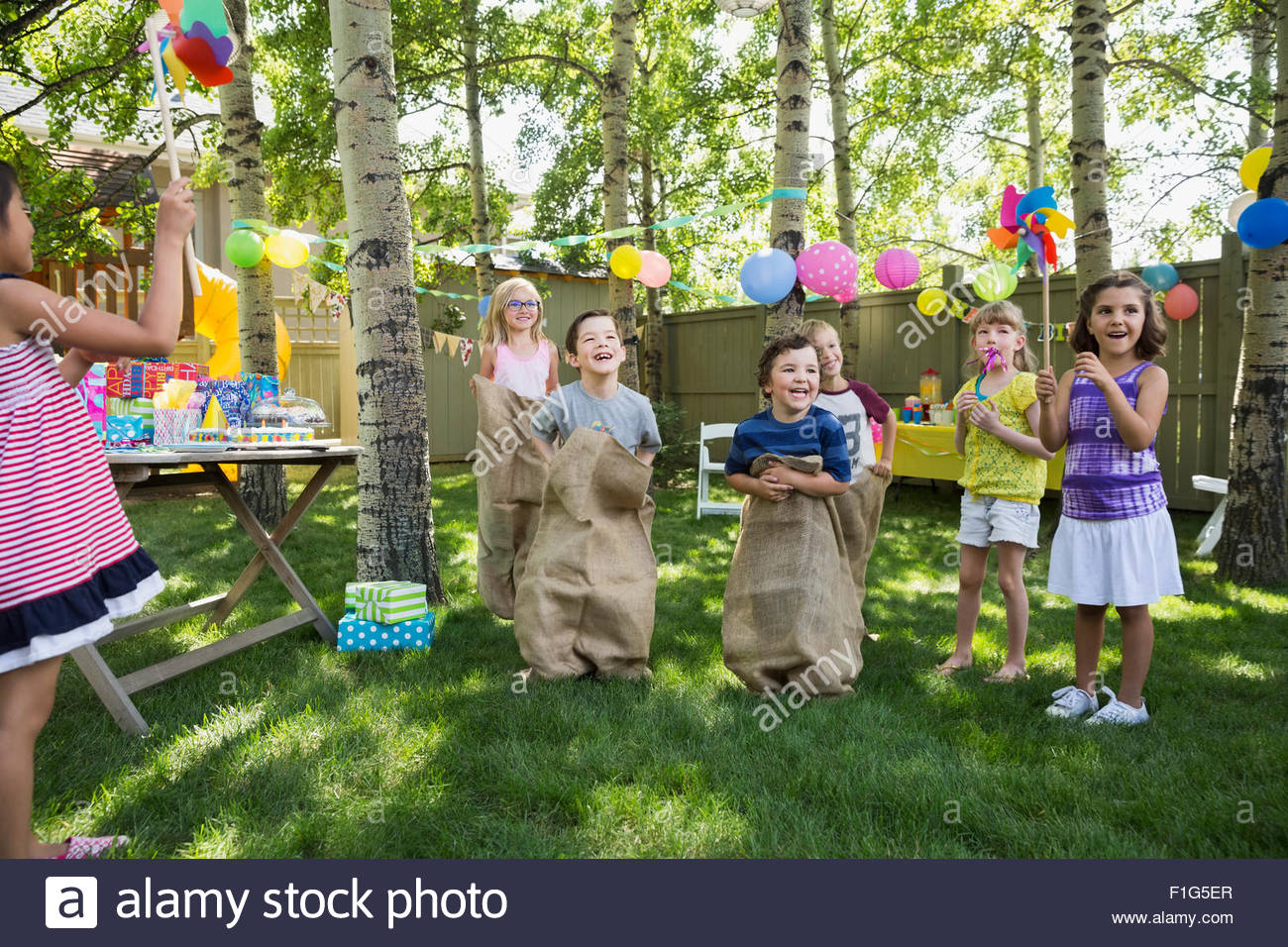 Kids enjoying sack race at backyard birthday party - Stock Image