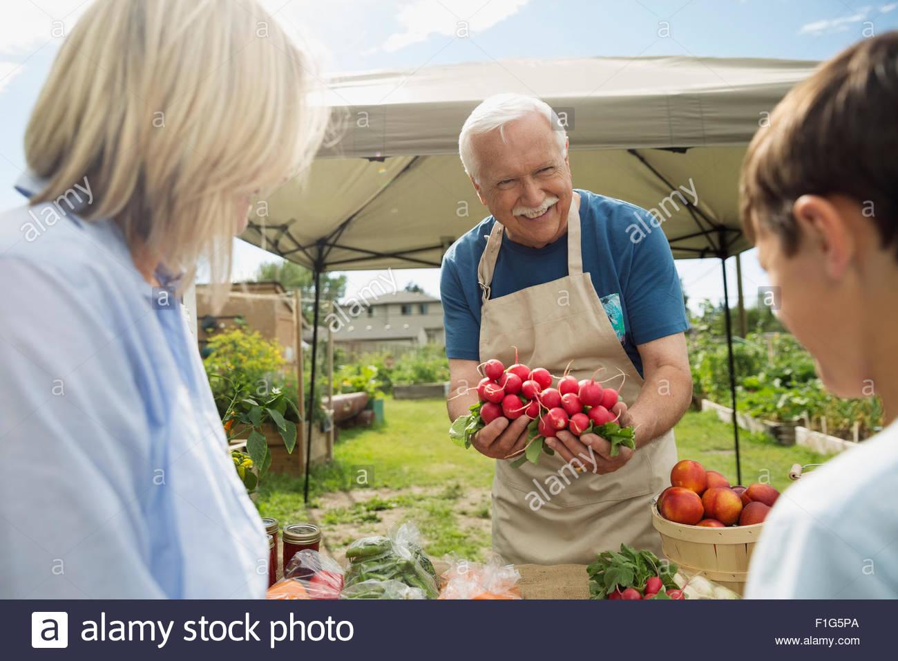 Proud farmer showing radishes boy farmers market stall - Stock Image