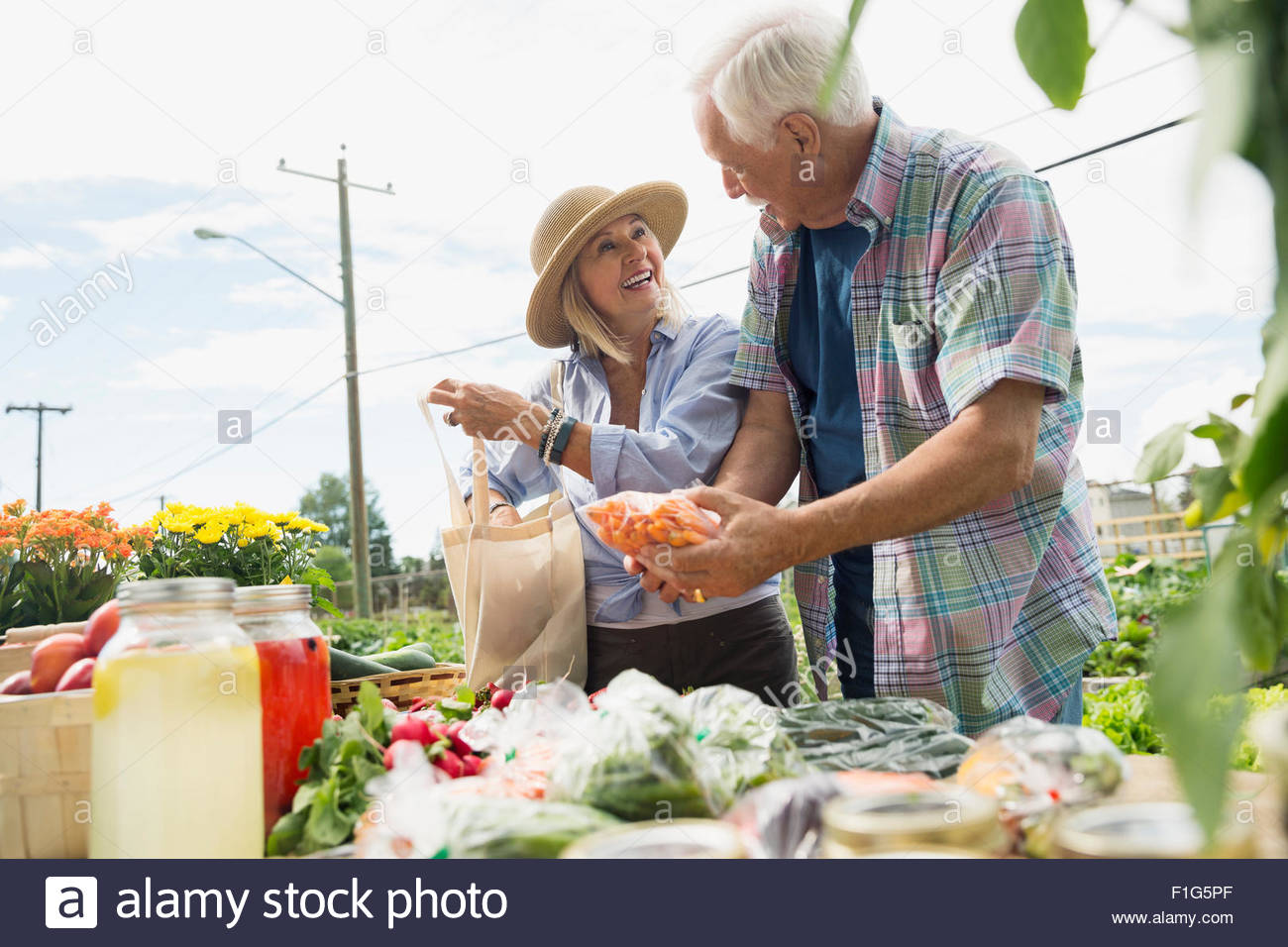 Couple shopping for fresh vegetables at farmers market - Stock Image