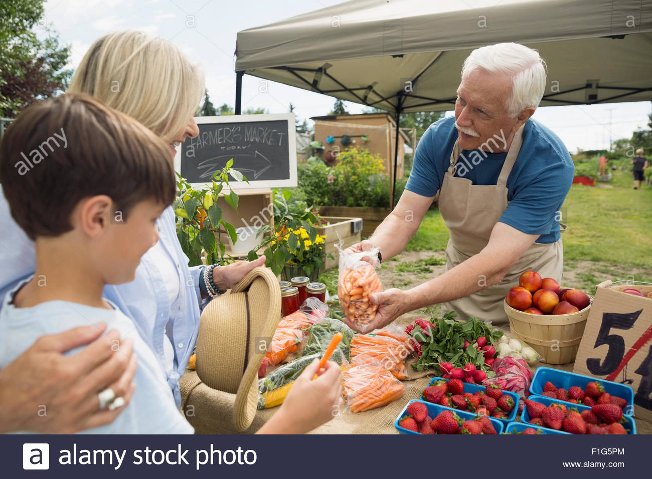 Farmer showing carrots to shoppers farmers market stall - Stock Image