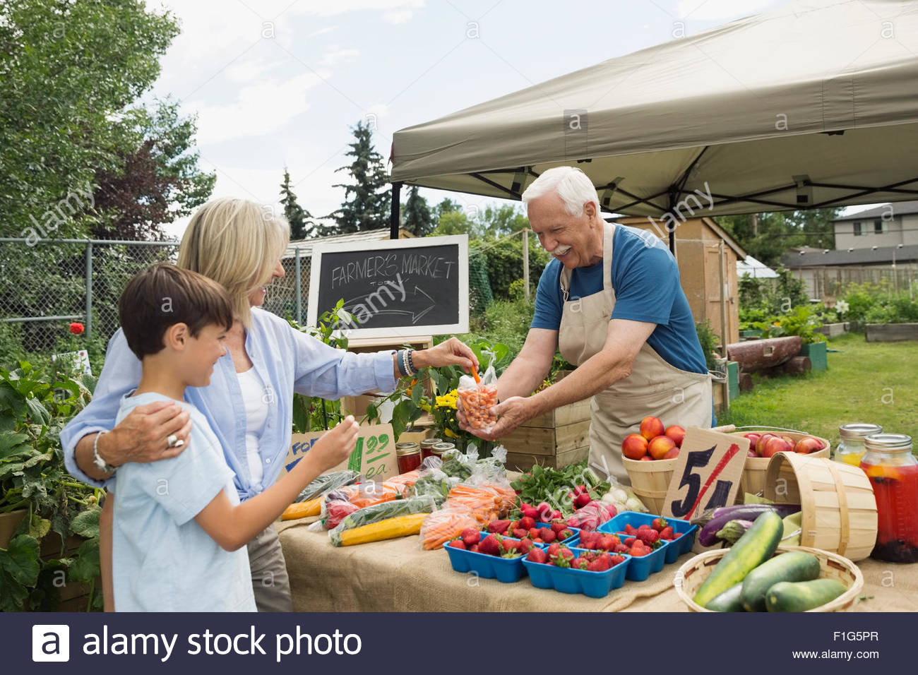 Farmer offering carrots to customers farmers market stall - Stock Image