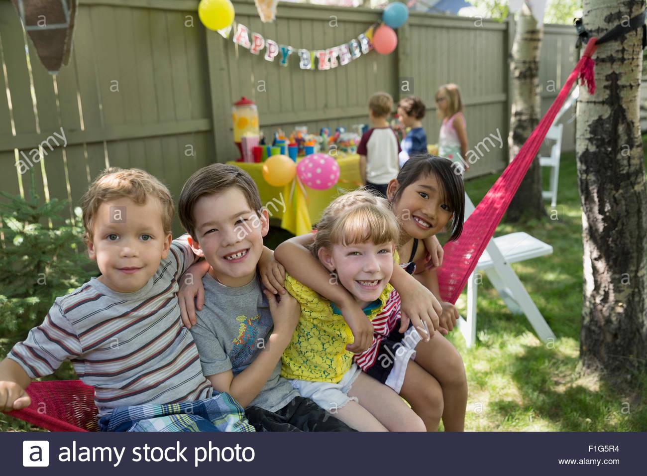 Portrait smiling kids hammock backyard birthday party - Stock Image