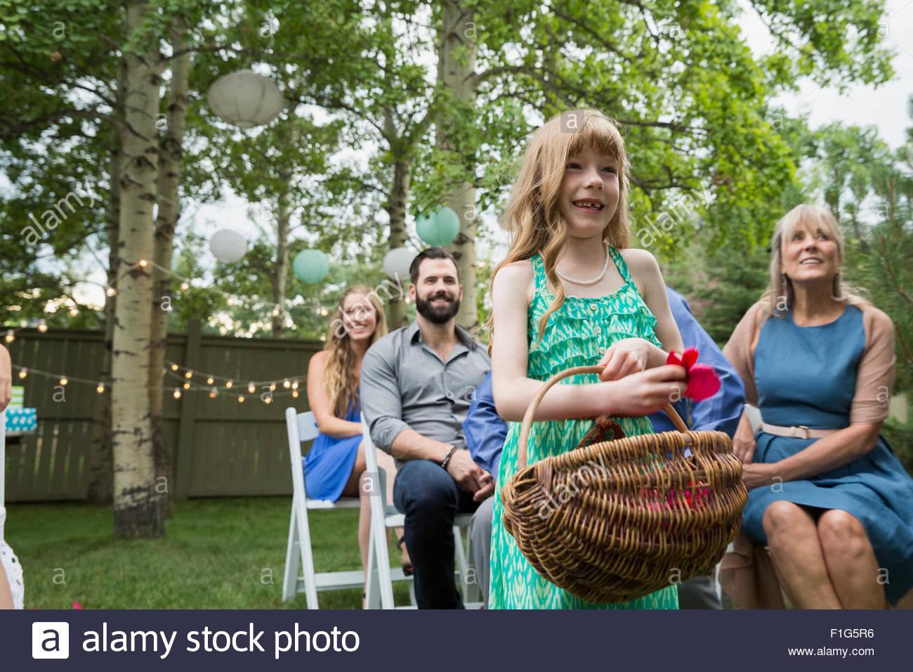 Smiling flower girl with basket at backyard wedding - Stock Image