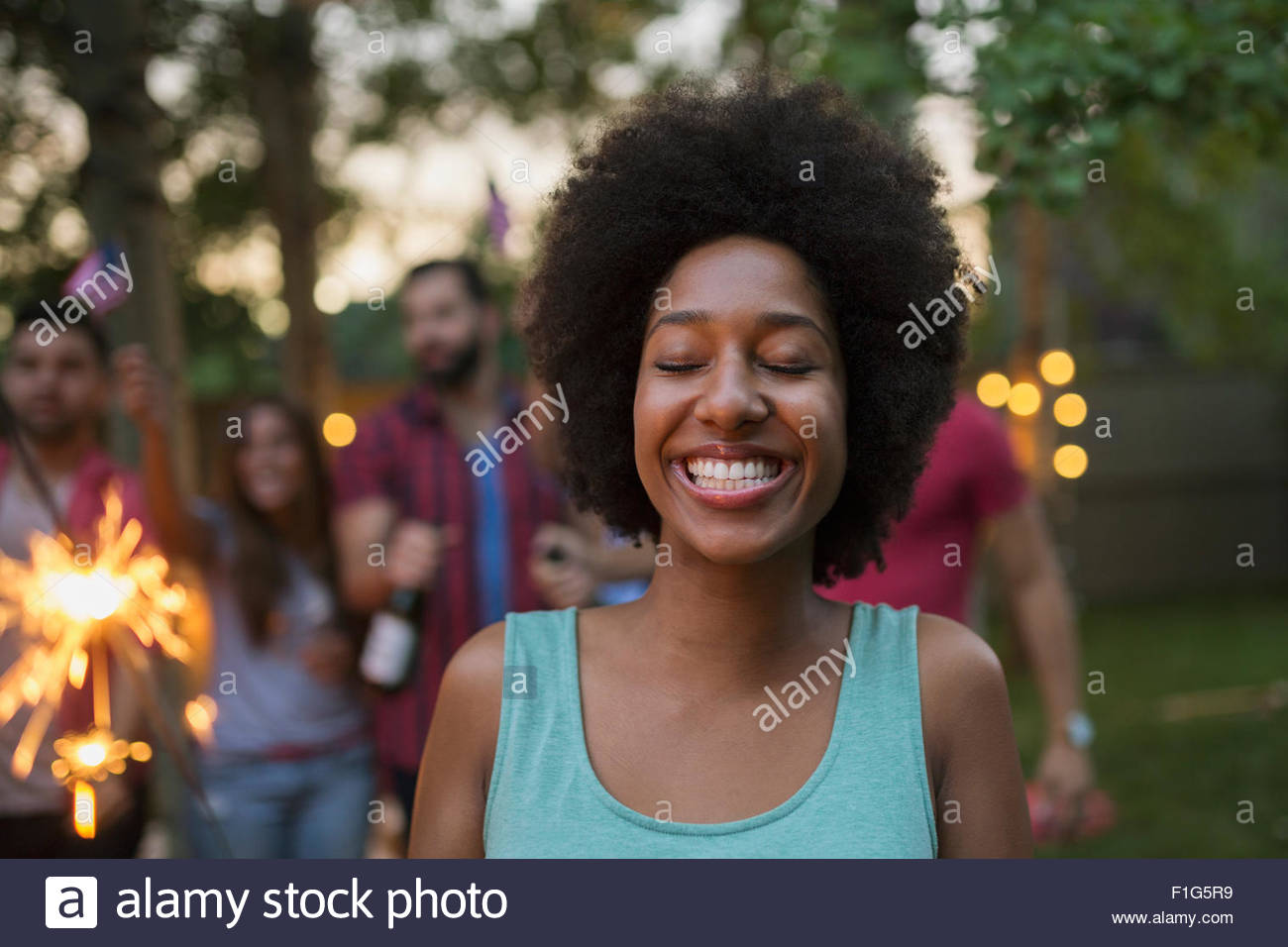 Enthusiastic woman with eyes closed holding sparkler backyard - Stock Image