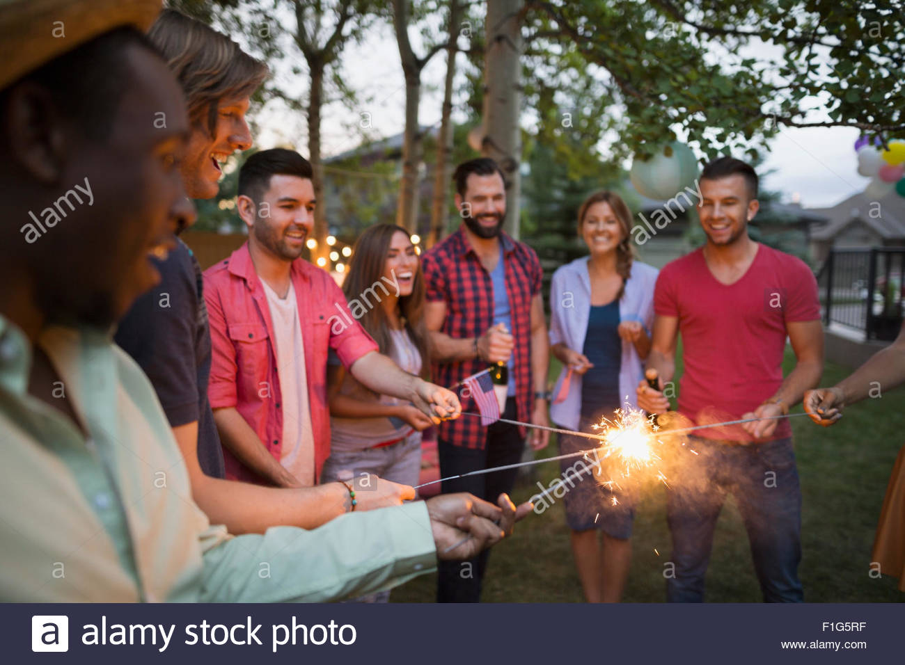 Friends lighting sparklers backyard 4th of July party - Stock Image