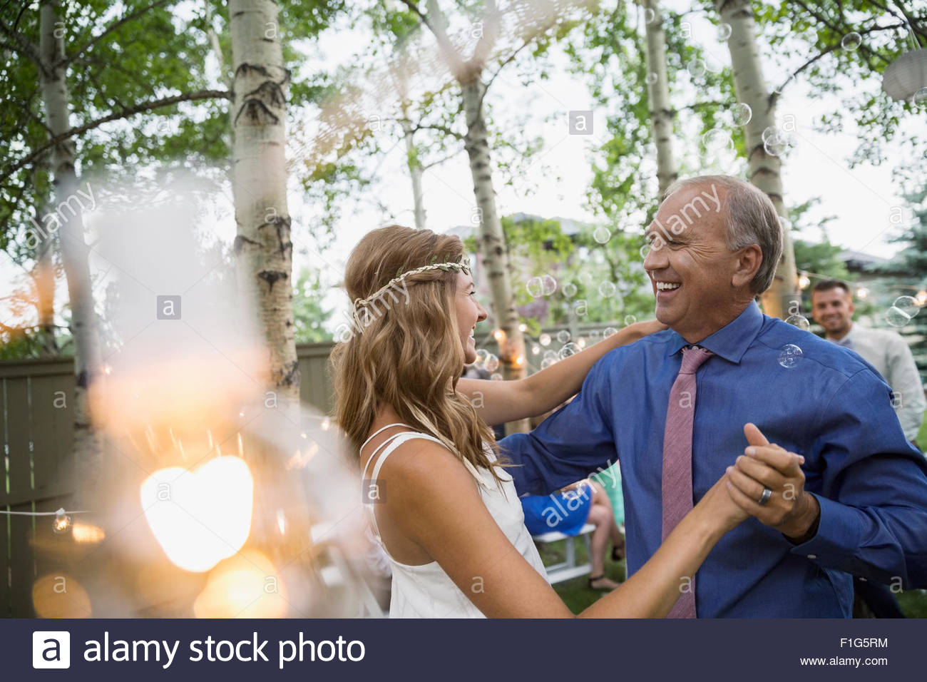 Bride and father dancing at backyard wedding reception - Stock Image