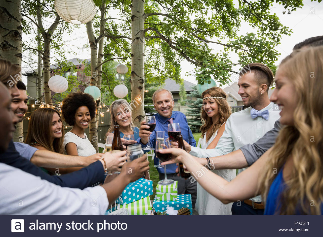 Bride, groom and wedding guests toasting drinks reception - Stock Image