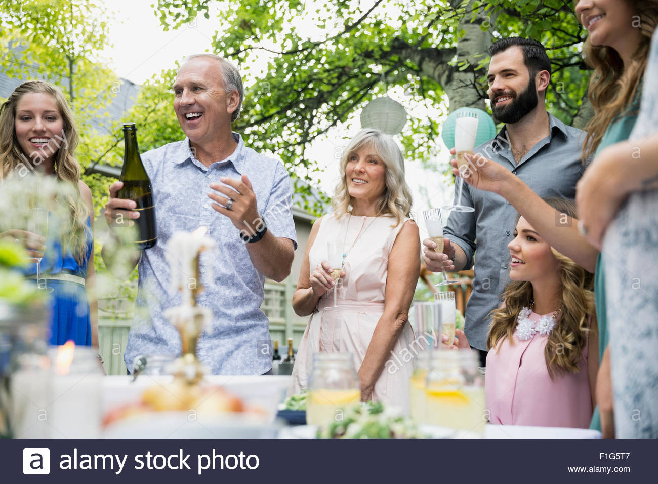Family drinking celebrating with champagne at garden party - Stock Image