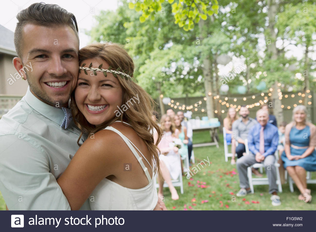 Portrait enthusiastic bride and groom at backyard wedding - Stock Image
