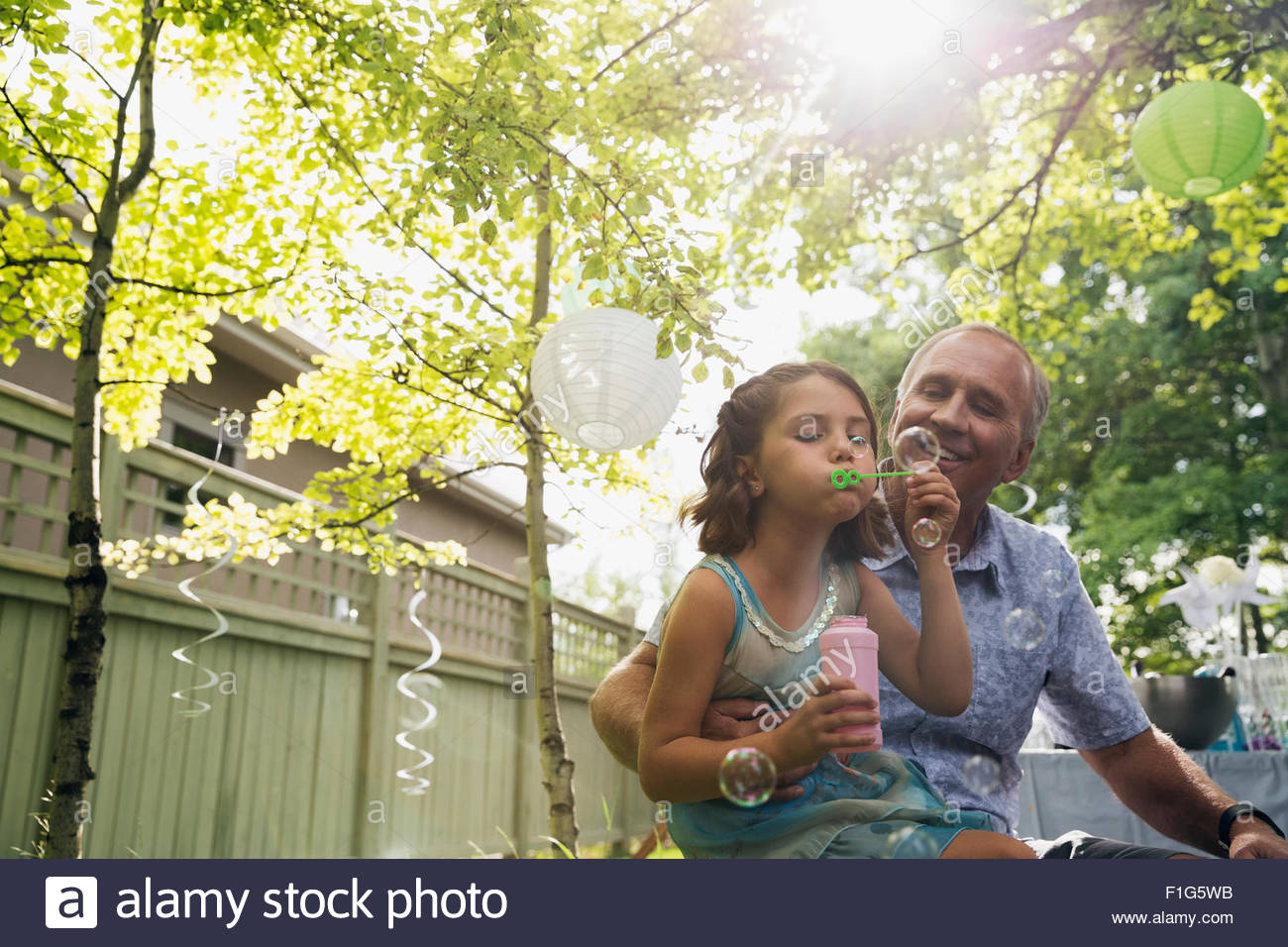 Grandfather watching granddaughter blow bubbles backyard - Stock Image