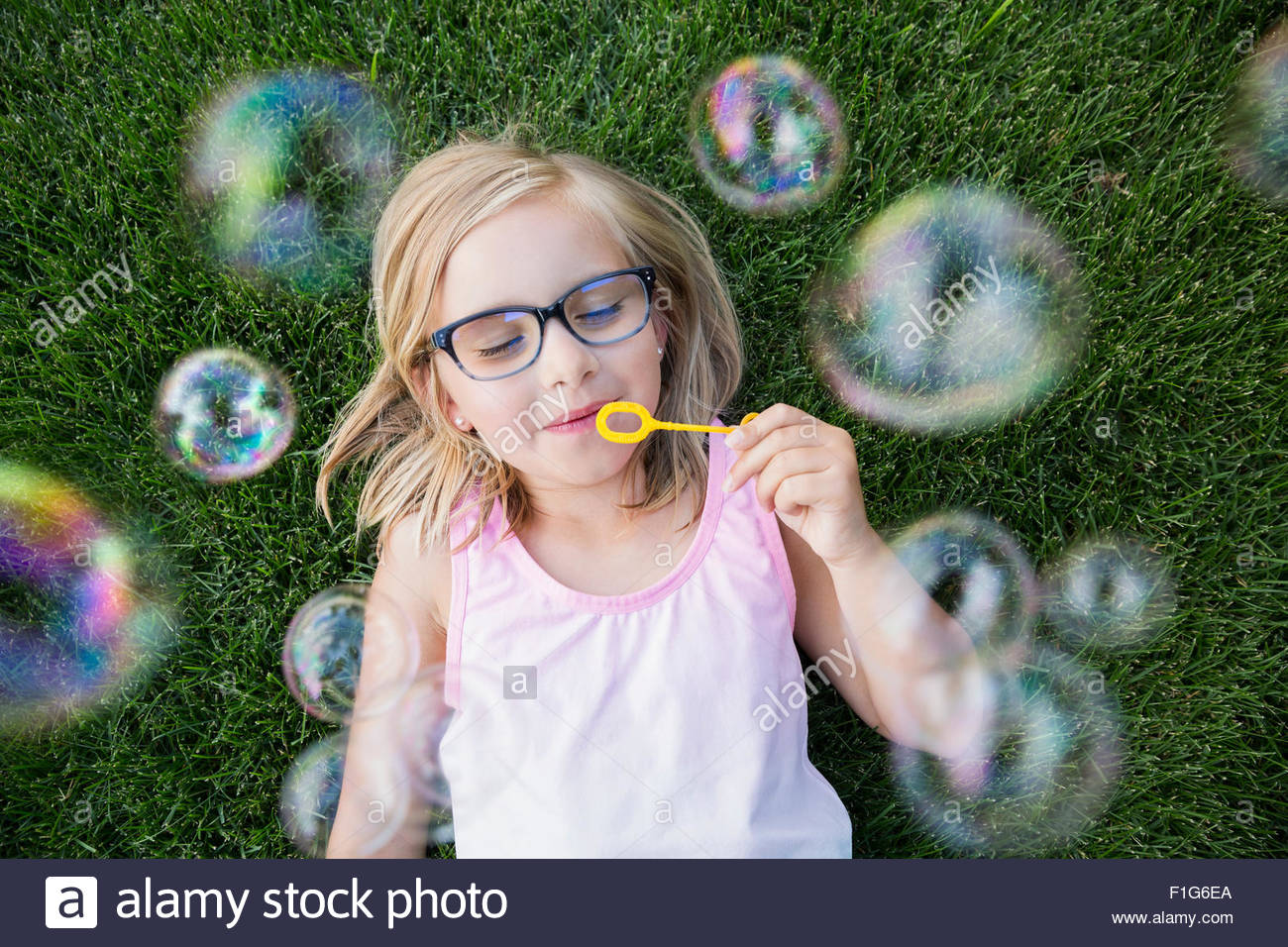 Overhead view blonde girl with eyeglasses blowing bubbles - Stock Image
