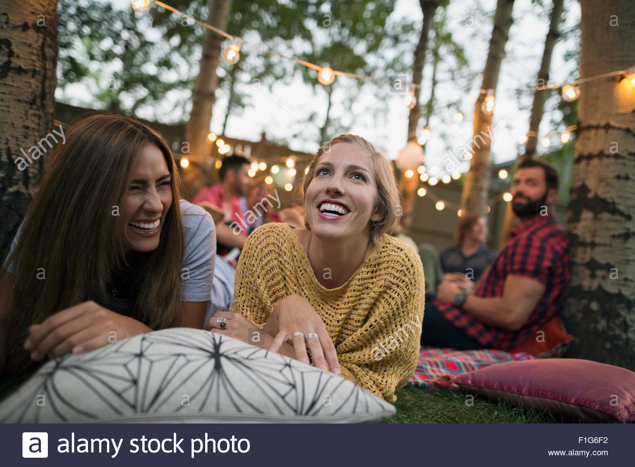 Smiling women relaxing on cushion at backyard party - Stock Image