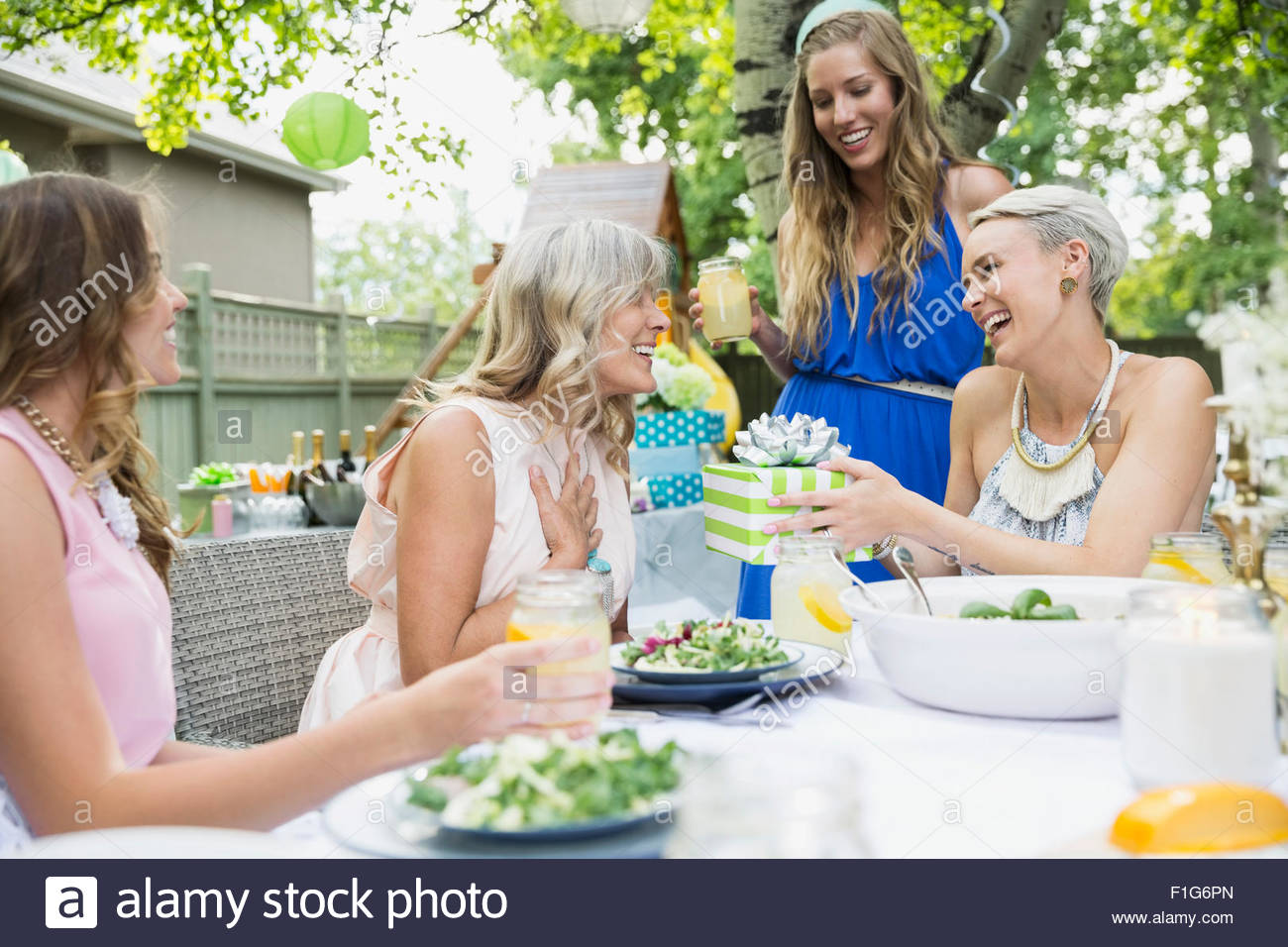 Woman receiving birthday gift at garden party lunch - Stock Image