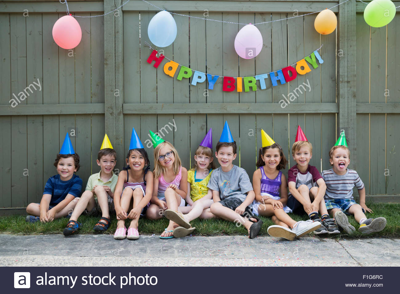 Portrait smiling kids a row backyard birthday party - Stock Image