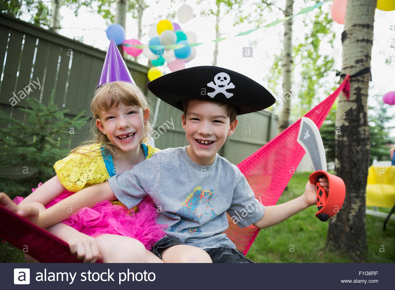 Portrait smiling brother and sister costumes on hammock - Stock Image