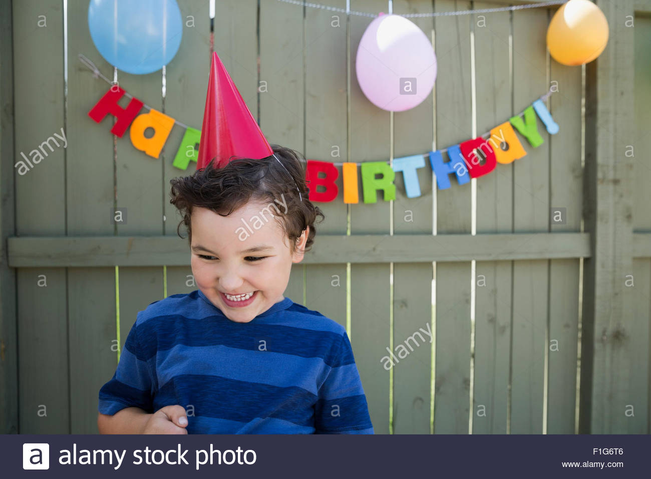 Enthusiastic boy wearing birthday party hat - Stock Image