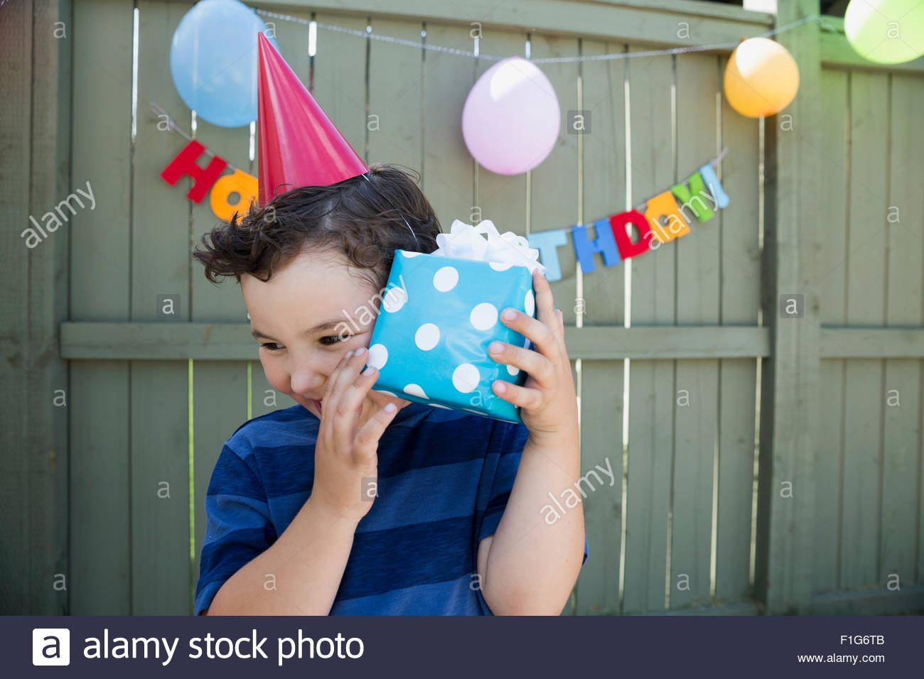 Boy wearing birthday party hat shaking wrapped gift - Stock Image