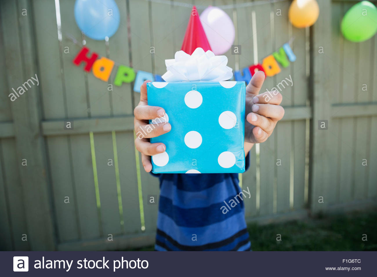 Boy holding polka-dot wrapped birthday gift - Stock Image