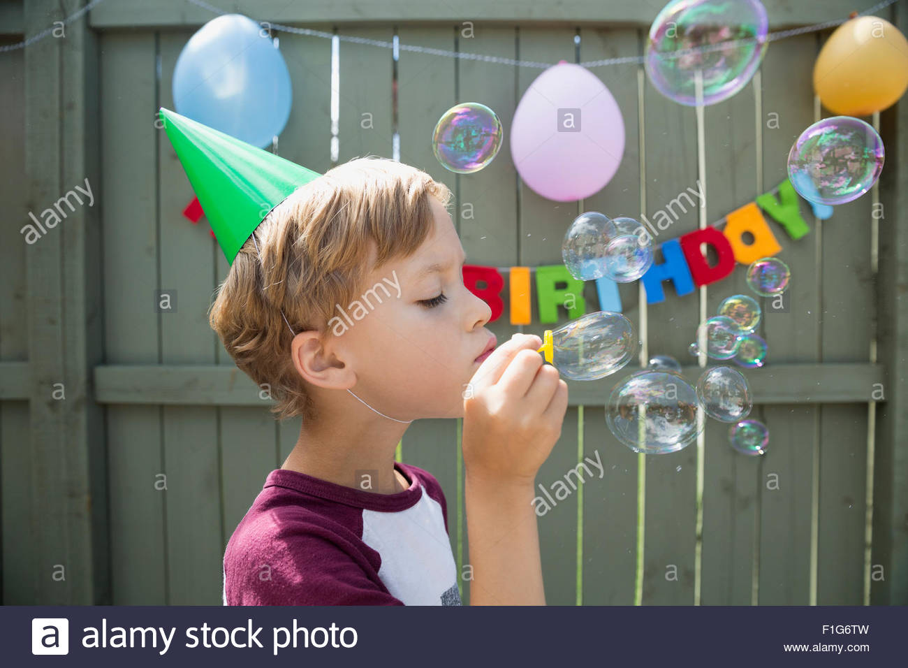 Boy wearing birthday party hat blowing bubbles - Stock Image