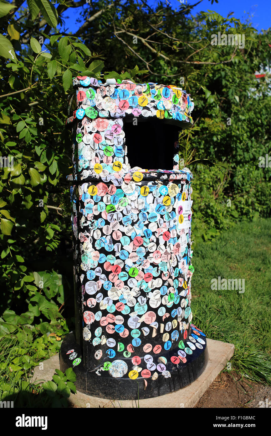 Litter bin festooned with sticky admission labels, Mevagissey, Cornwall, England, UK. - Stock Image