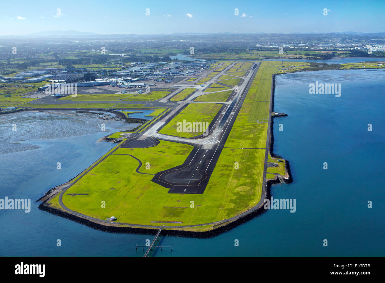 Main runway at Auckland Airport, and Manukau Harbour, Auckland, North Island, New Zealand - aerial - Stock Image