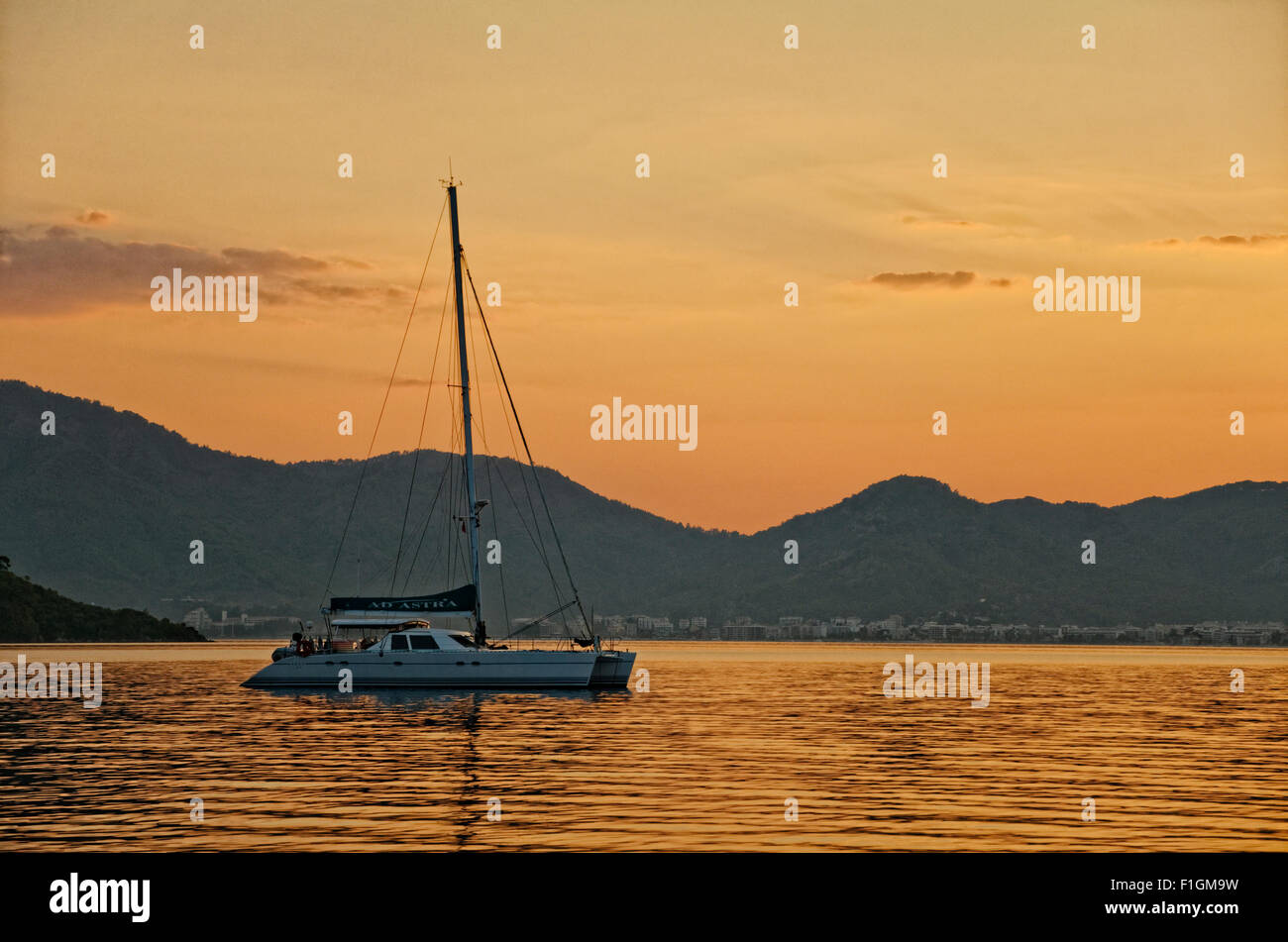 Catamaran anchored off-shore at sunset - Stock Image