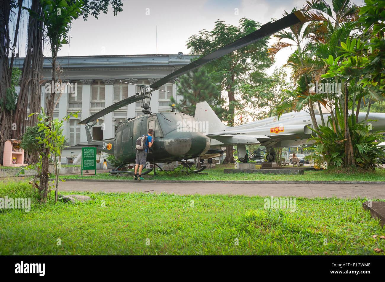 Tourist Vietnam, a curious visitor to the Ho Chi Minh City Museum in Saigon inspects the cockpit of a US Bell Huey - Stock Image