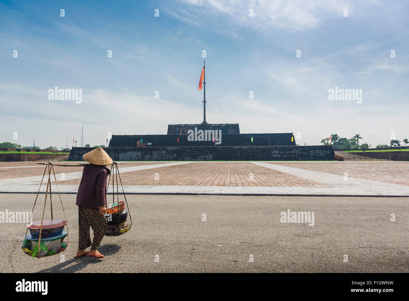 Hue Vietnam flag tower, a vendor carries her wares past the flag tower (Cot Co) near the Imperial Citadel in Hue, - Stock Image