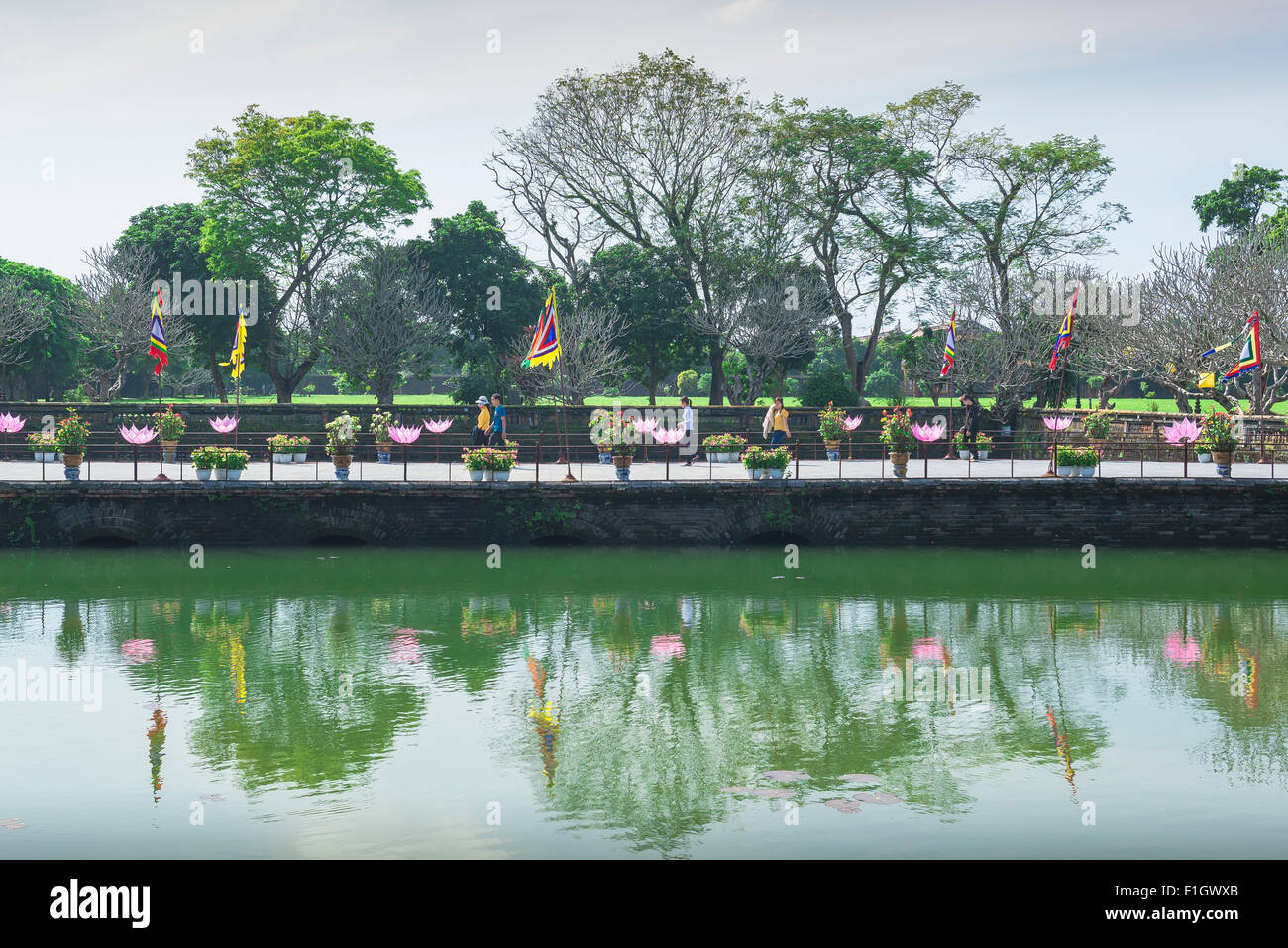 Hue Vietnam citadel, tourists walk alongside one of many lakes inside the Imperial Citadel in Hue, central Vietnam. - Stock Image