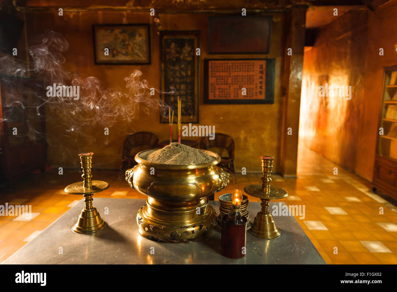Vietnam temple incense, in the Giac Vien Pagoda in north Cholon incense sticks planted in a brass urn gently smoulder, - Stock Image
